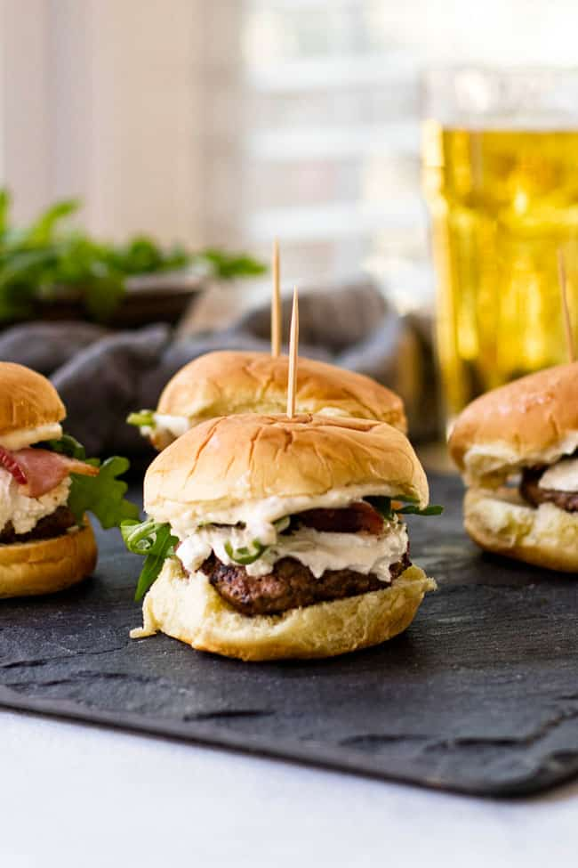 Bacon & Goat Cheese sliders with arugula and herb mayonnaise on a slate board
