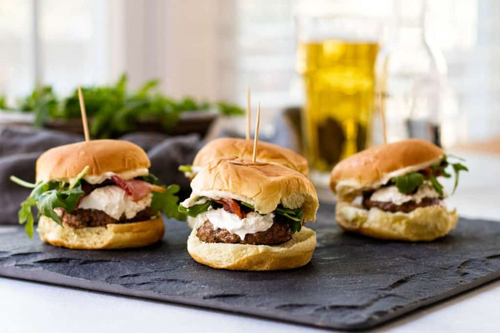 Four Bacon & Goat Cheese sliders with a glass of beer and fresh arugula in the background