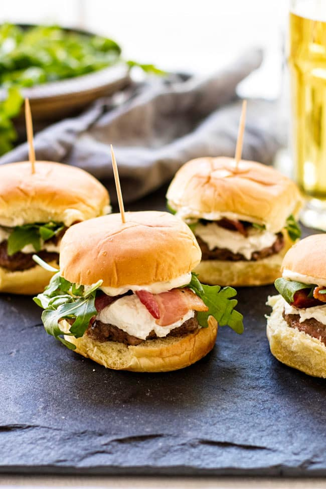 Four goat cheese and bacon sliders with a napkin and a glass of beer