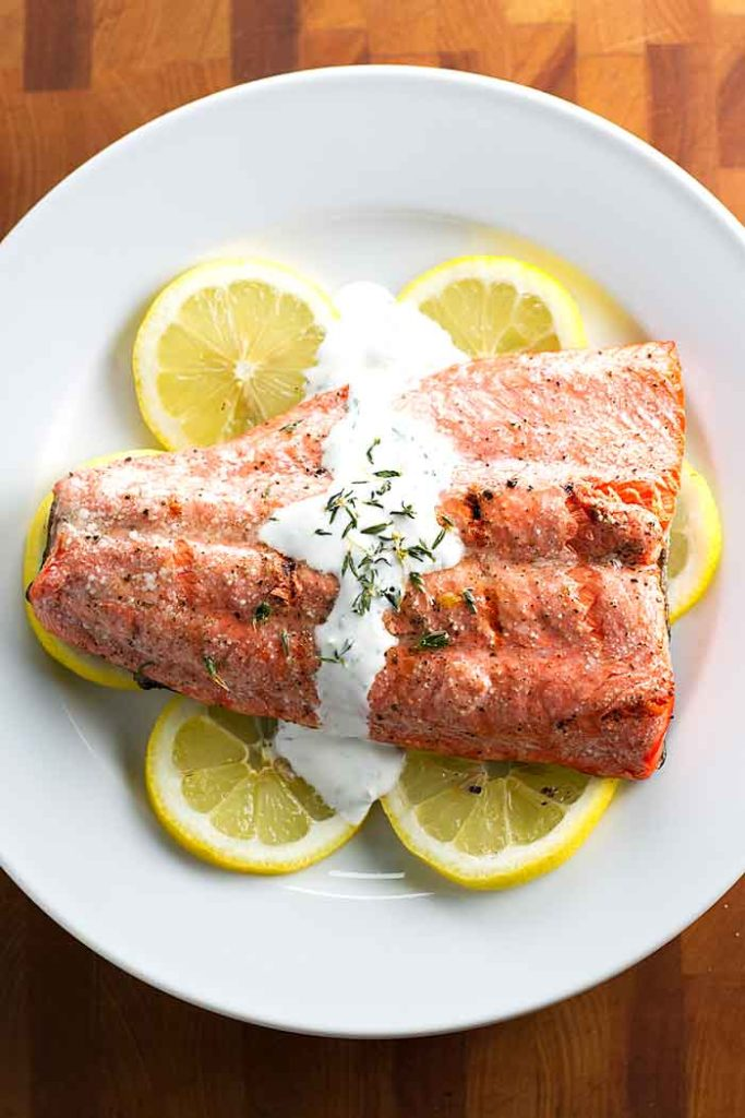 overhead photo of grilled salmon topped with cream sauce