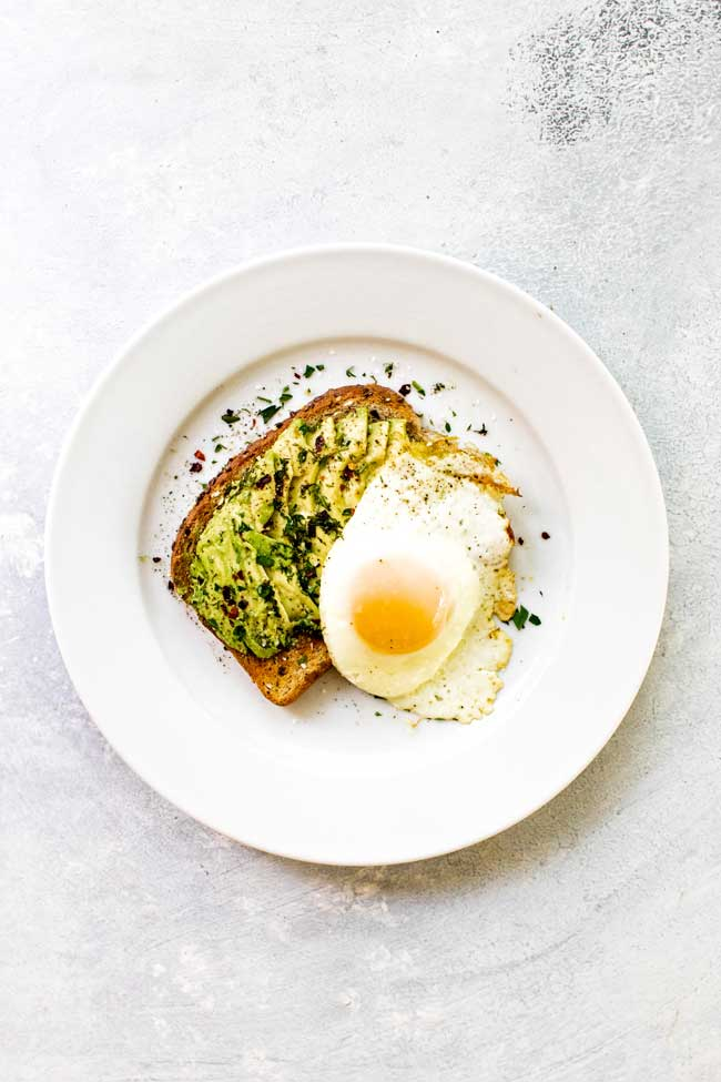 Toast topped with sliced avocado, fresh herbs, and a sunny-side up egg on a white plate