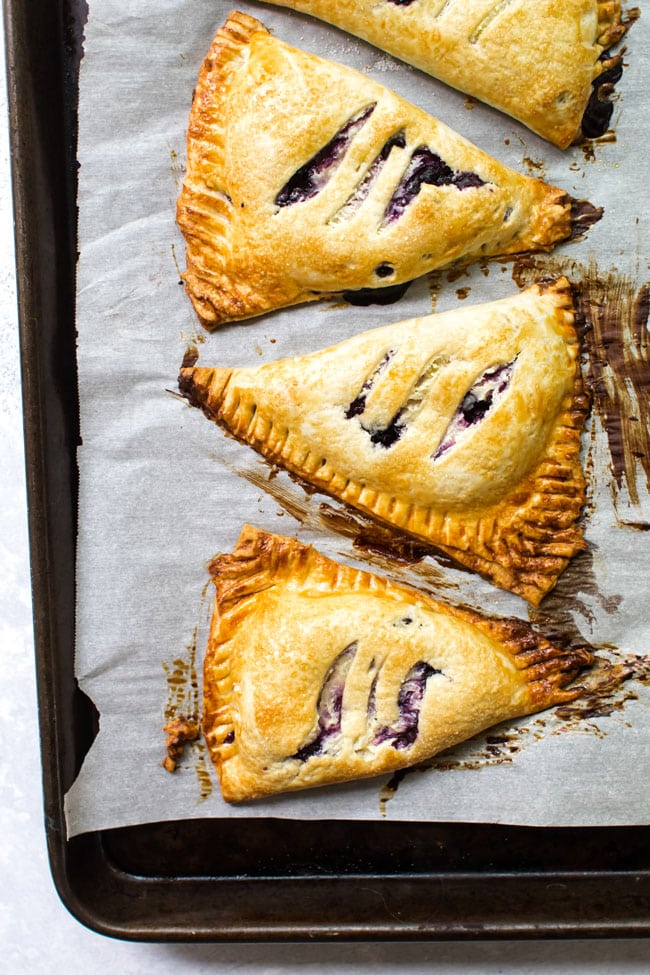 Three blueberry hand pies on a baking sheet lined with parchment paper