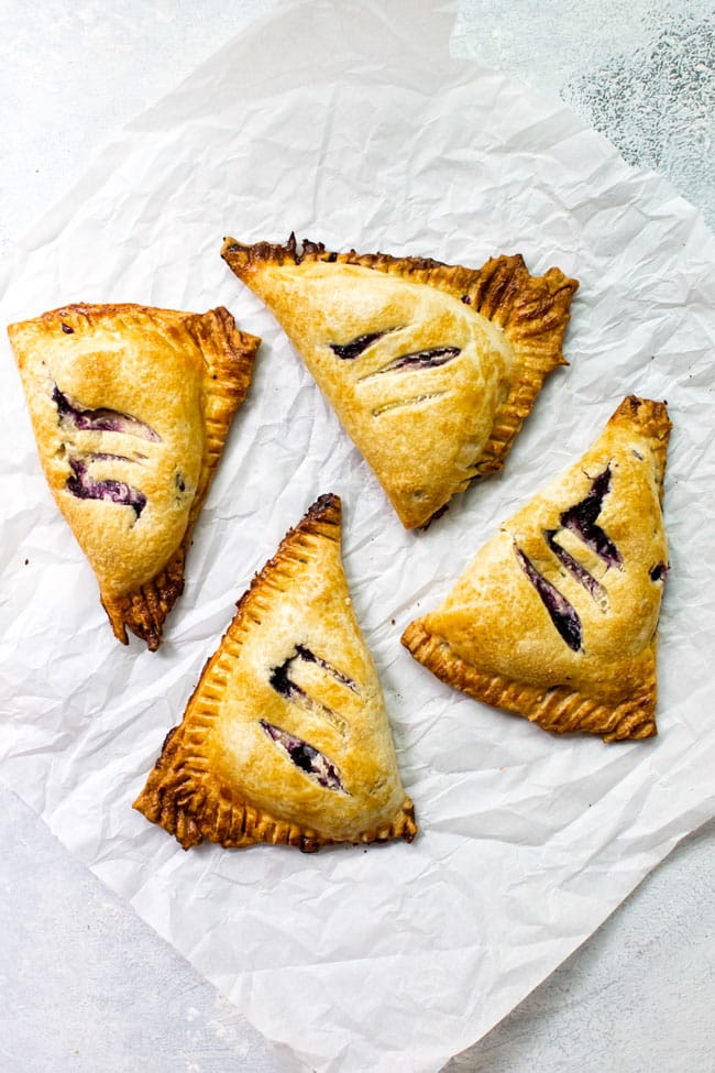 Four blueberry hand pies on parchment paper