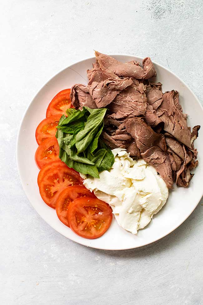 Ingredients for caprese roast beef sandwiches on a white plate