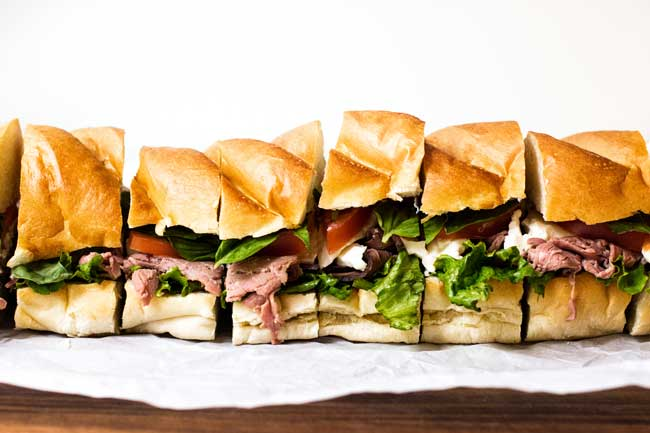 Slice caprese roast beef sandwiches lined up on a cutting board