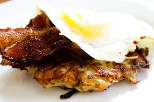 rosemary potato pancake topped with bacon and a fried egg