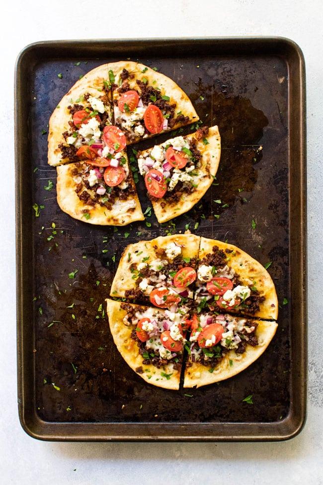Two Chorizo and Goat Cheese Pita Pizza on a sheet pan