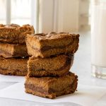 stacked peanut butter and chocolate bars with a glass of milk