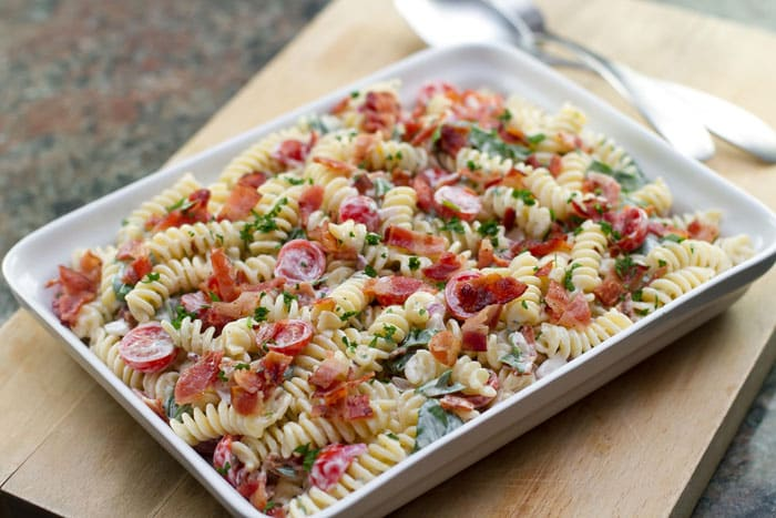 BLT Pasta Salad in a white dish on a cutting board
