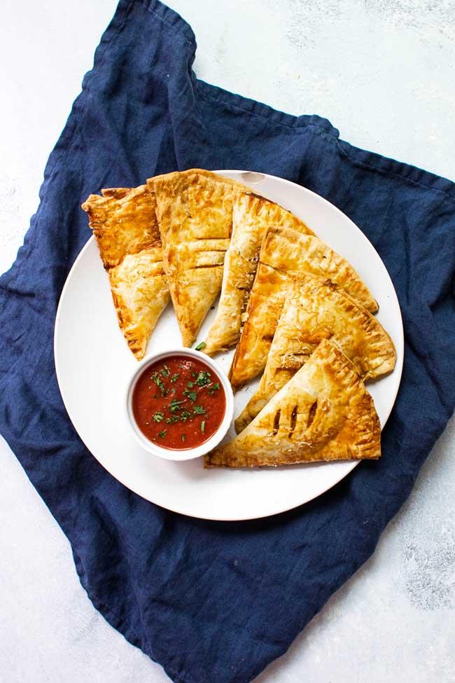 Savory Hand Pies on a white plate with marinara sauce