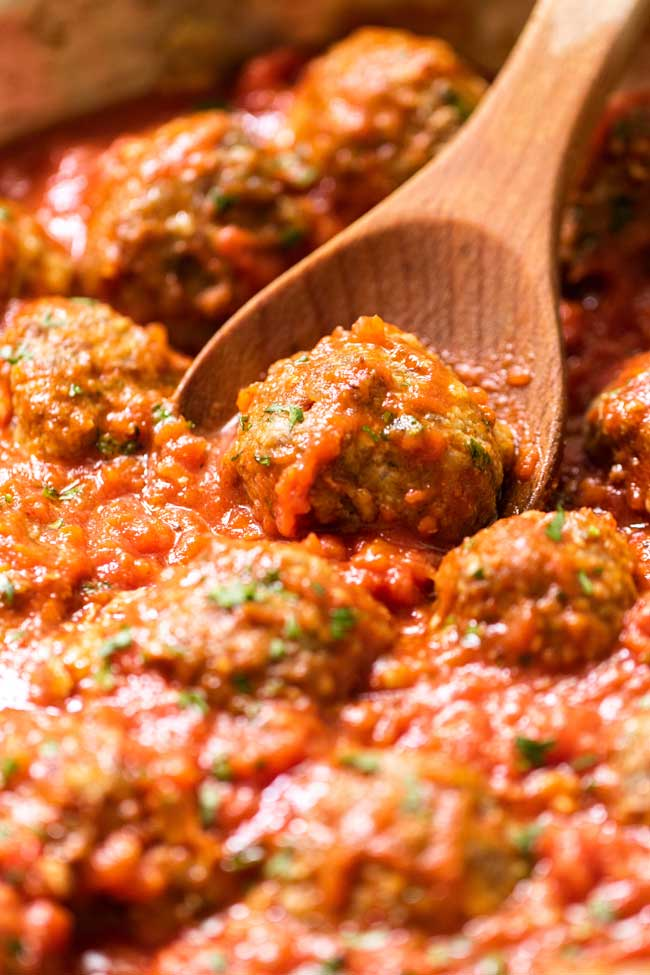 Close-up photo of a meatball in sauce
