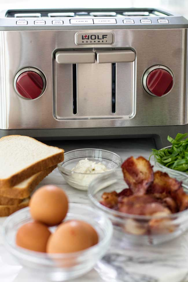 a photo of a wolf gourmet toaster with bread, eggs, and bacon