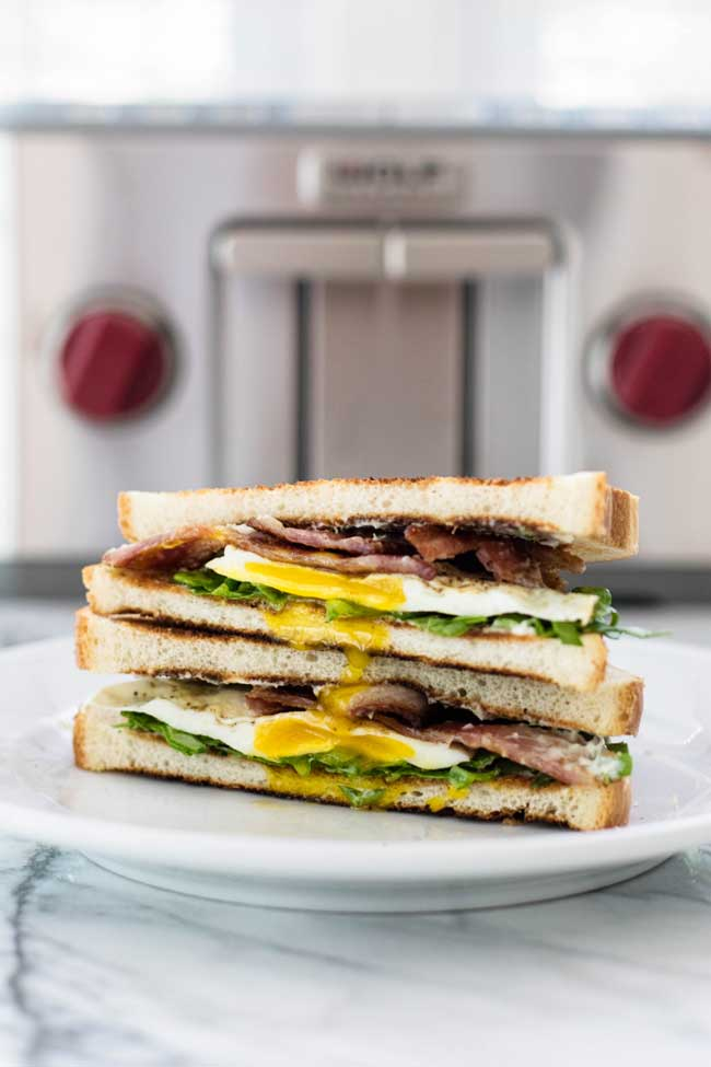 two halves of a fried egg sandwich stacked on a white plate with a toaster in the background