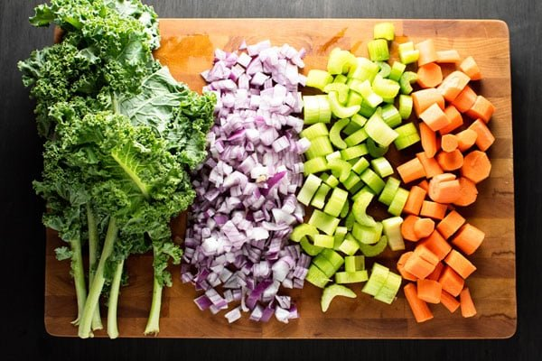 Raw kale, onion, celery, and carrots on a cutting board