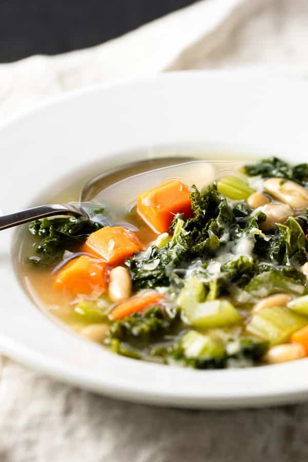 Hearty Veggie Soup with White Beans and Kale in a white bowl with a spoon