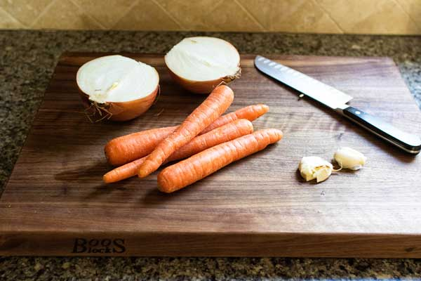 raw carrots, onion, and garlic on a wooden cutting board