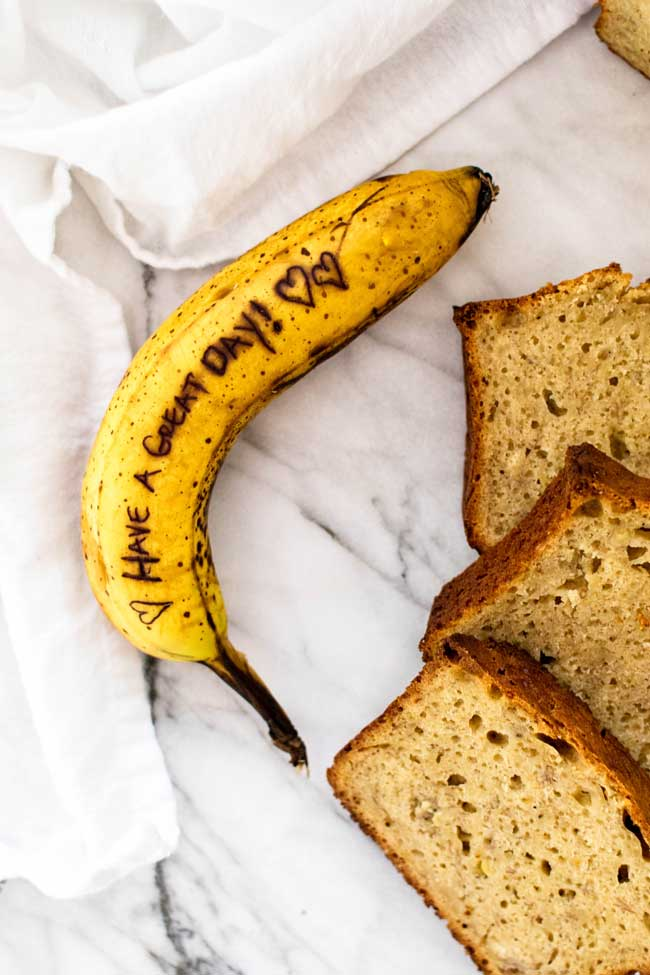 overhead photo of a banana with a message written on it