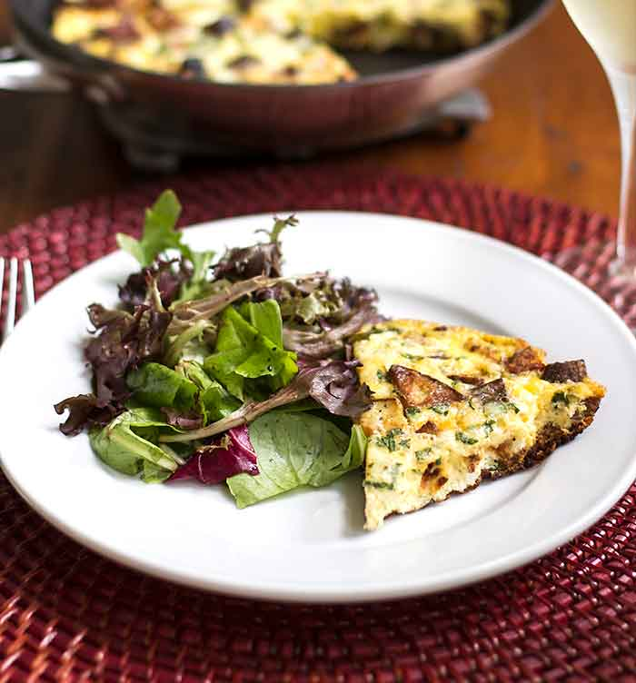 close-up photo of a slice of Chorizo Potato Frittata with a green salad on the side