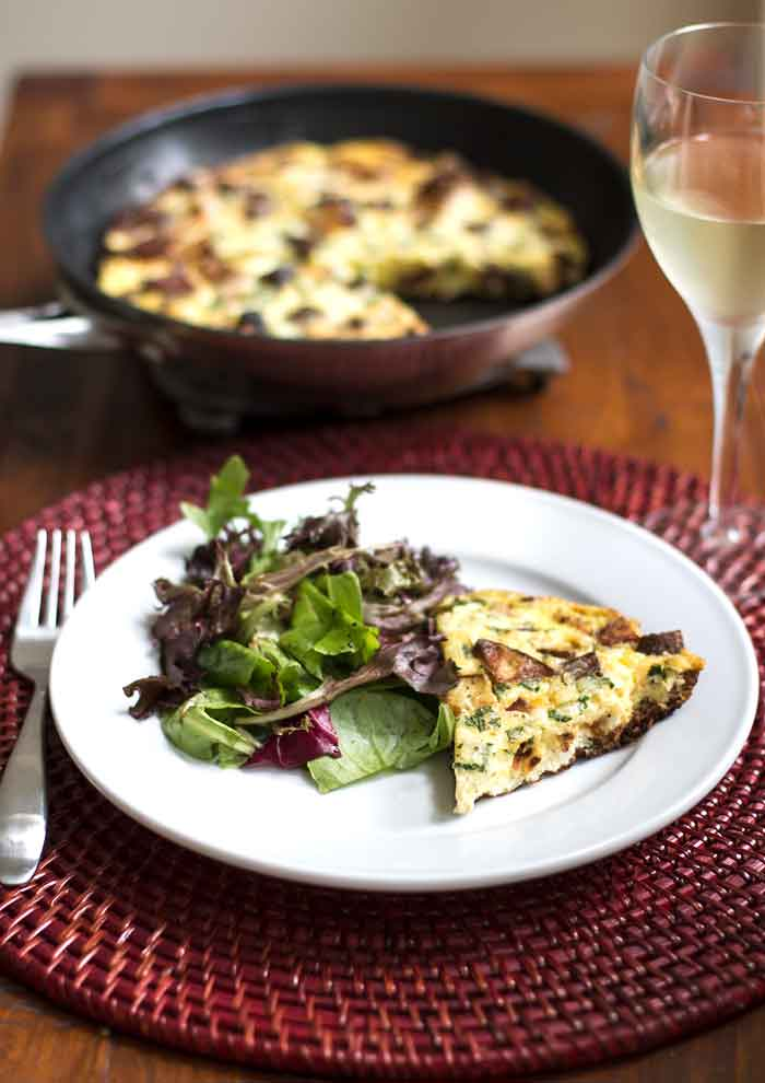 Chorizo Potato Frittata with a glass of wine and a green salad