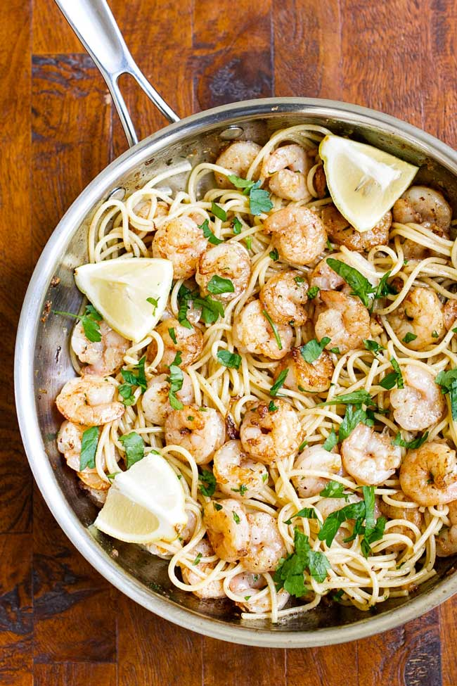 Pasta tossed in garlic butter with shrimp in a large skillet with lemon wedges as garnish