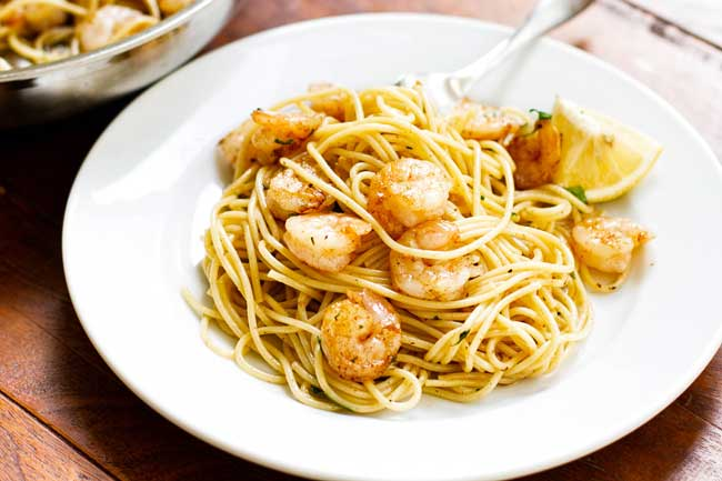 Garlic butter shrimp pasta on a white plate with a fork