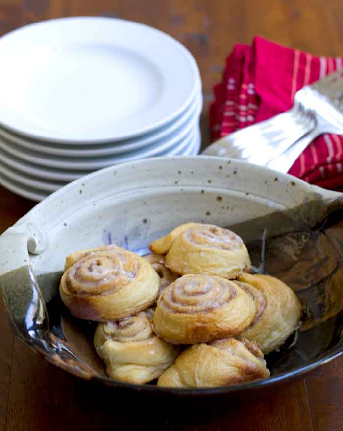 Easy mini cinnamon rolls in a bowl with a stack of plates and forks in the background