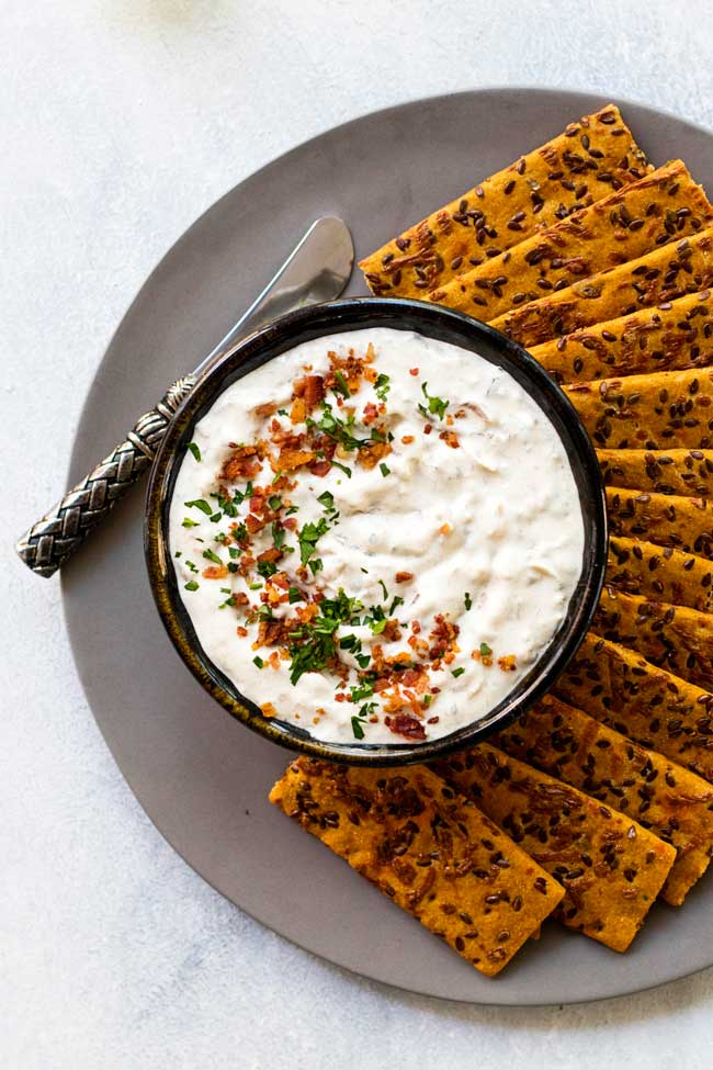 Onion dip garnished with bacon and parsley on a plate with crackers