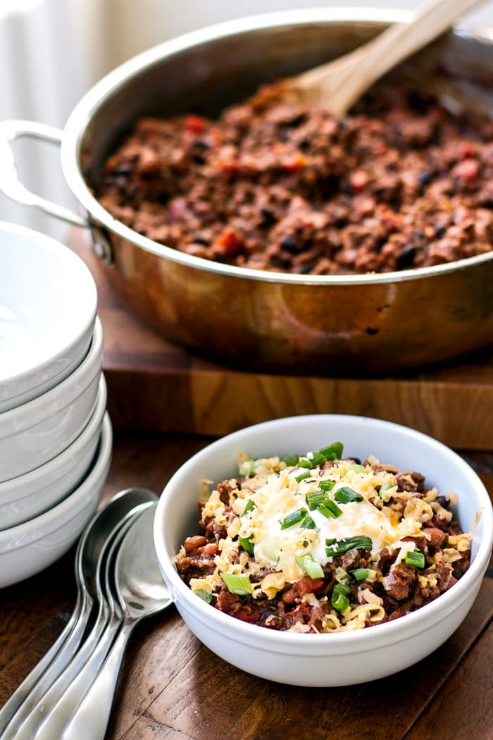 Easy ground beef chili in a bowl garnished with sour cream, cheese, and green onions
