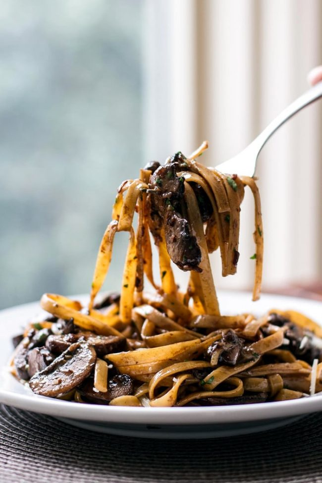 Balsamic mushroom pasta on a white plate with the pasta twirled onto a fork