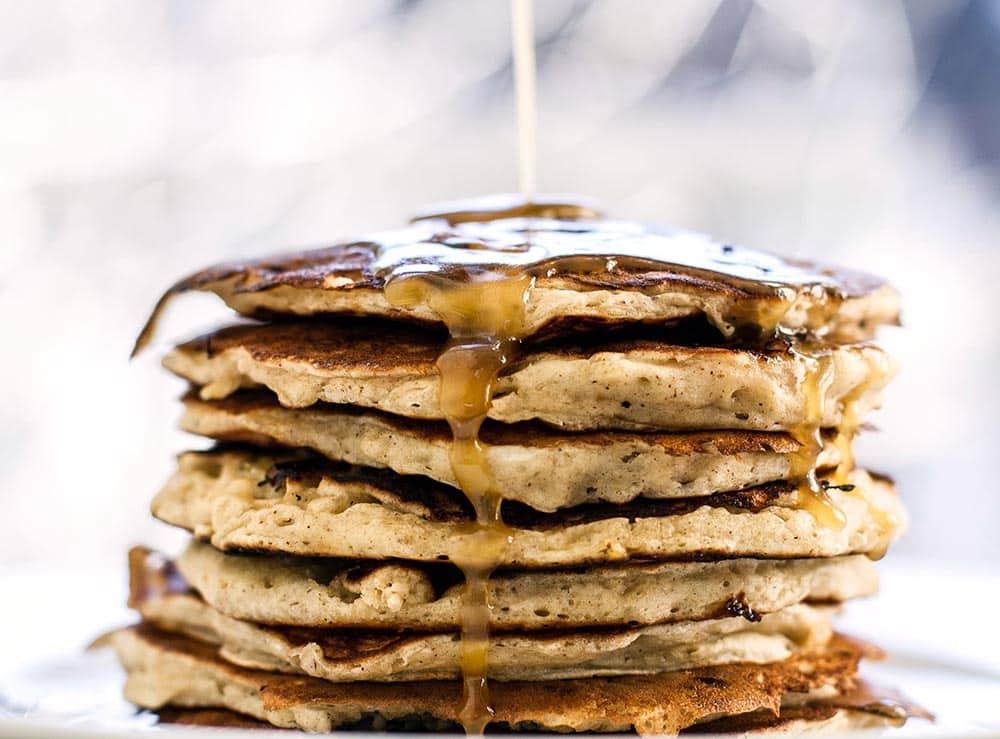 Banana pancakes on a plate with maple glaze dripping down