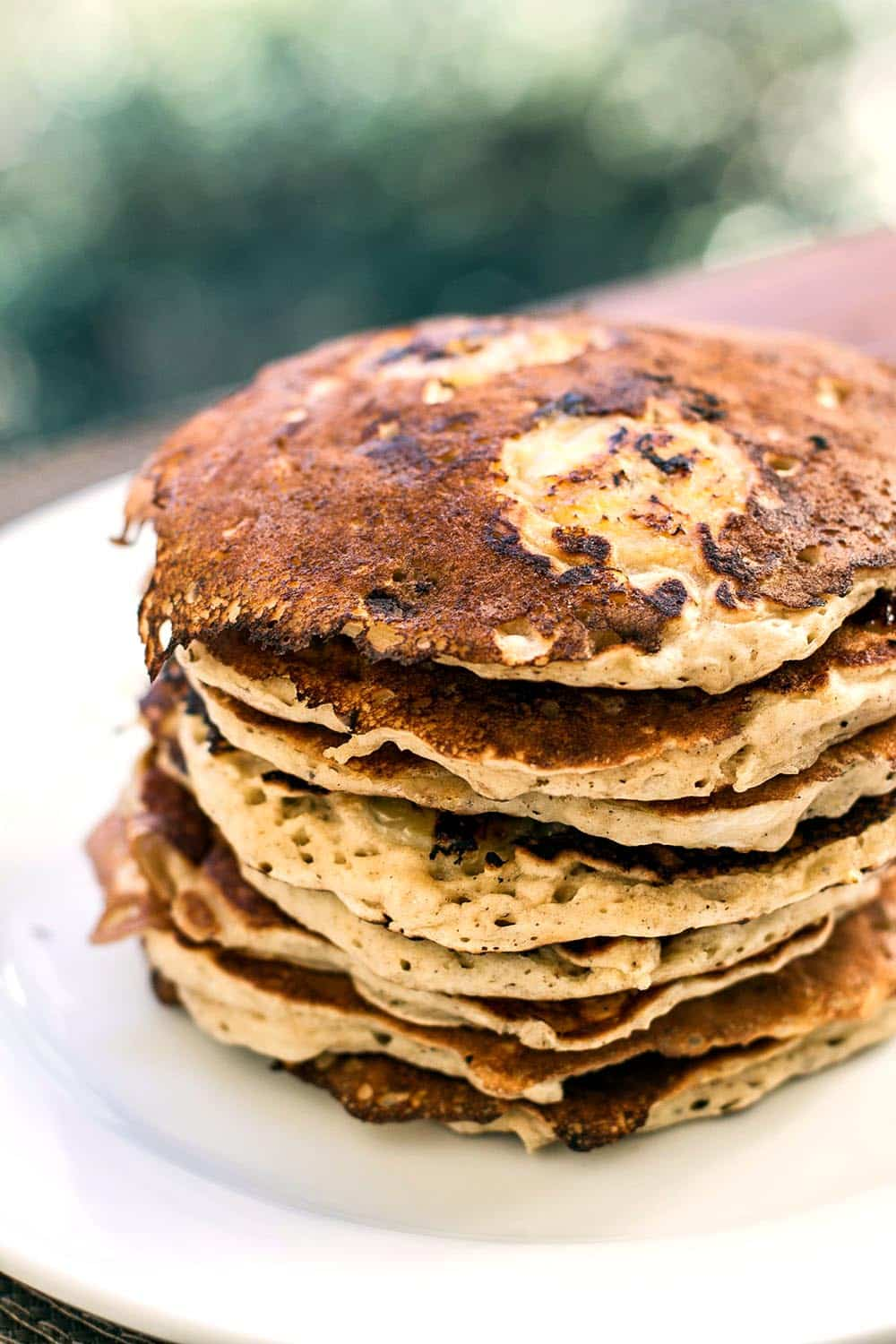 A stack of banana pancakes on a white plate