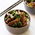 beef and broccoli in a grey bowl with chopsticks