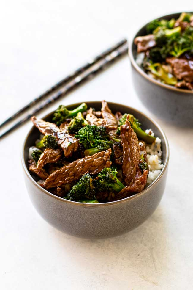 Two bowls of beef and broccoli with chopsticks