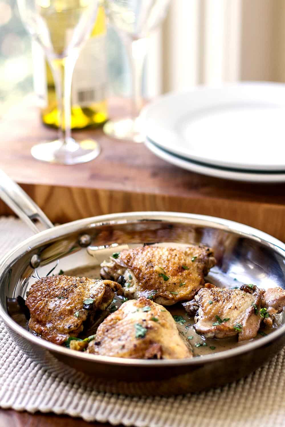Chicken thighs in a skillet with rosemary wine sauce with white plates in the background
