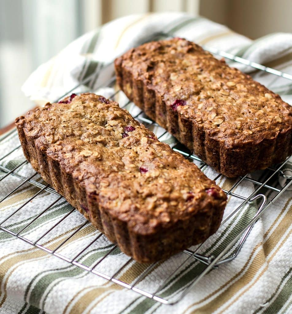 Two loaves of Cranberry Banana Oat Bread on a baking rack