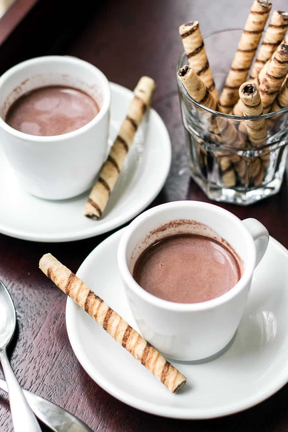 Quick and easy hot chocolate in two white mugs with saucers and cookies on the side