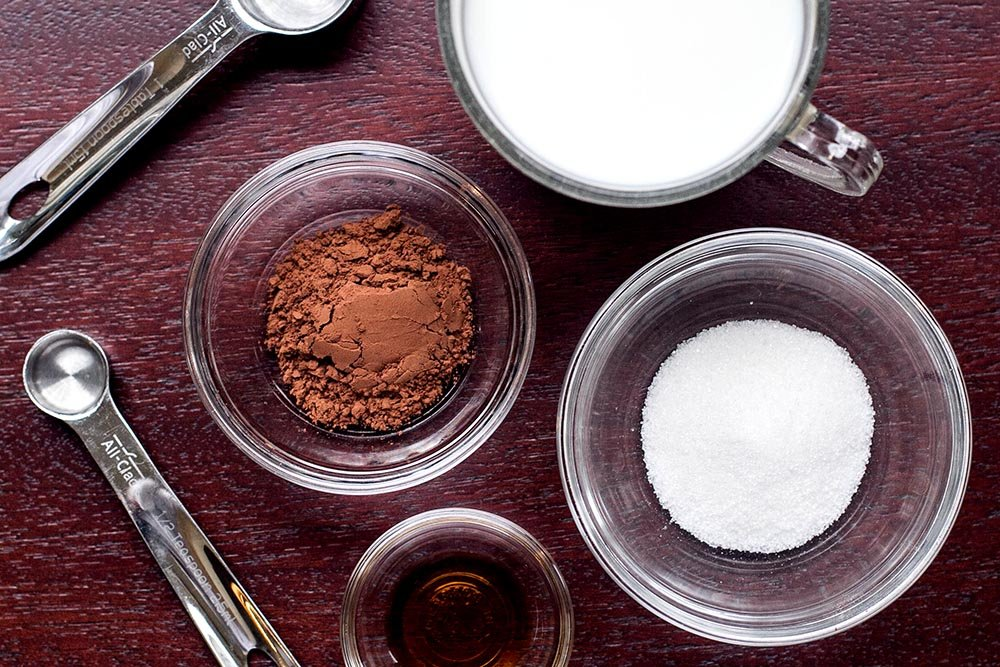 Ingredients for quick and easy hot chocolate. A bowl of cocoa powder, a bowl of sugar, a measuring cup of milk, and a small bowl of vanilla