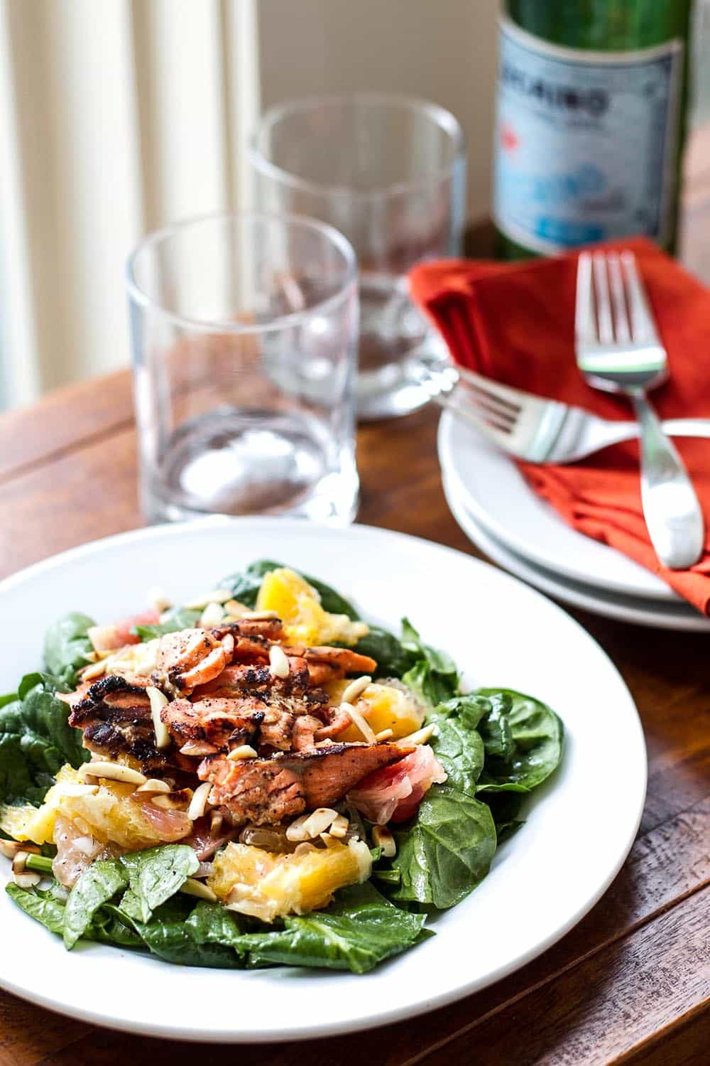 A light and refreshing salad with spinach, citrus, grilled salmon, and toasted walnuts.