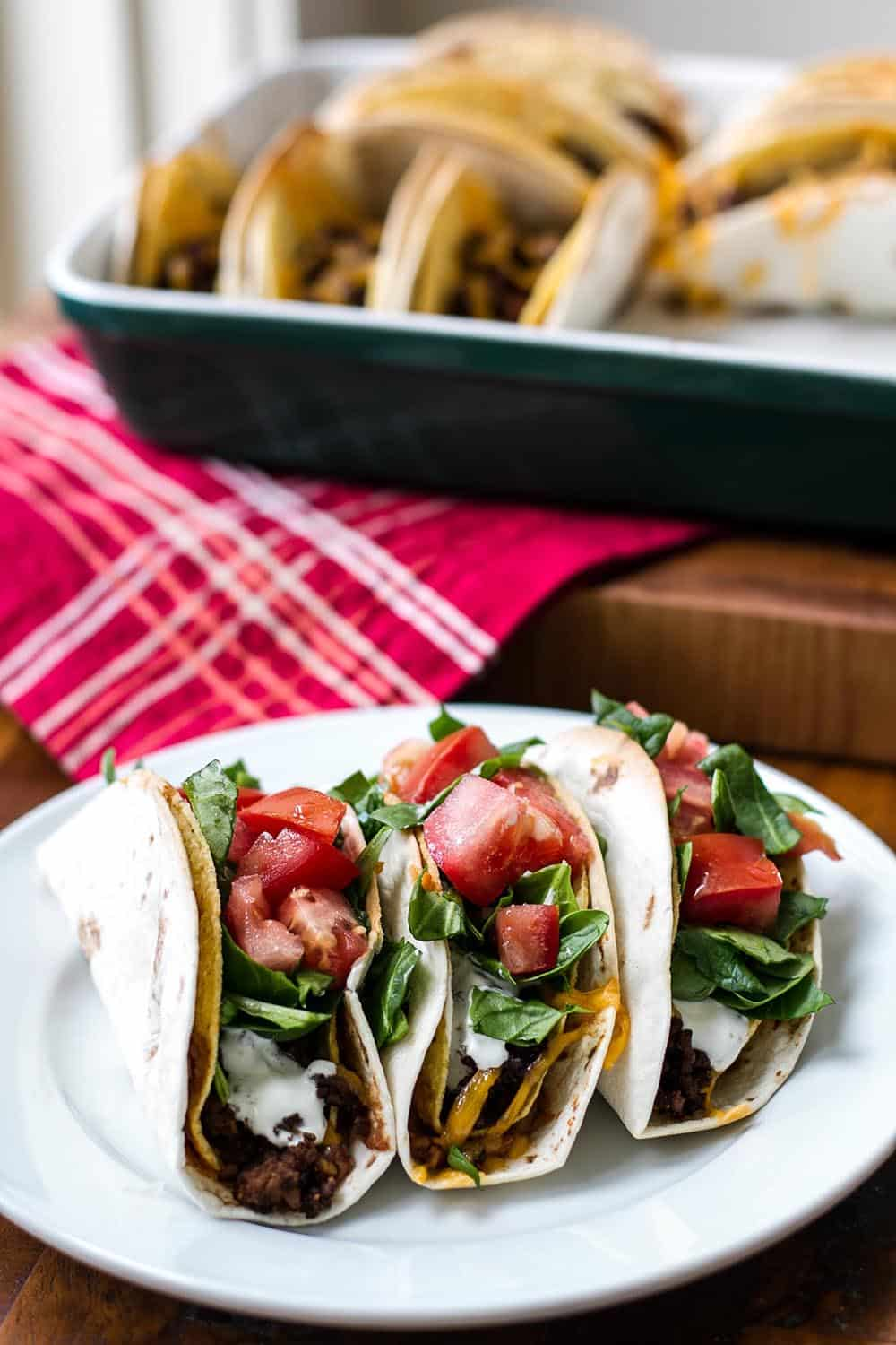 Baked double decker tacos on a white plate with a baking dish in the background
