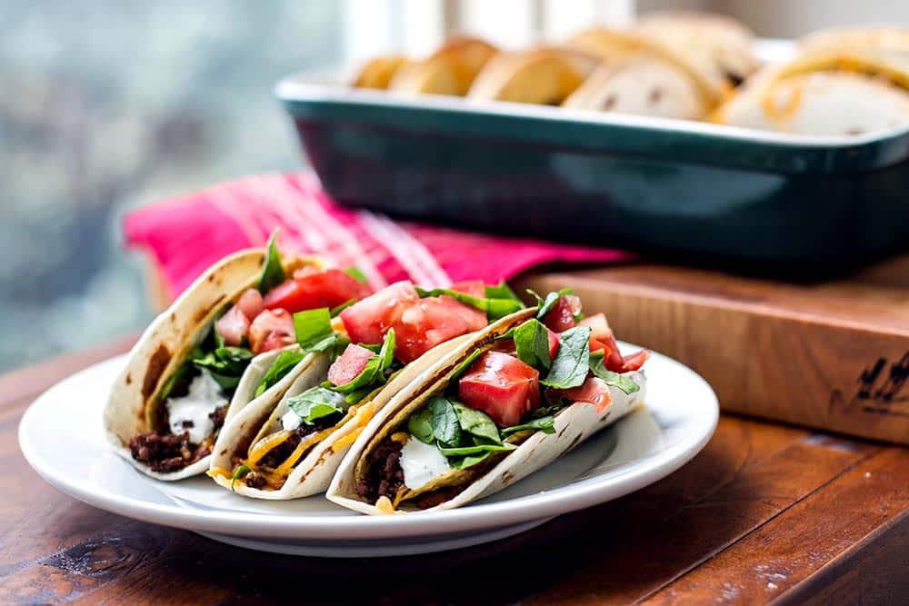 Three baked double decker tacos on a plate topped with lettuce and tomatoes