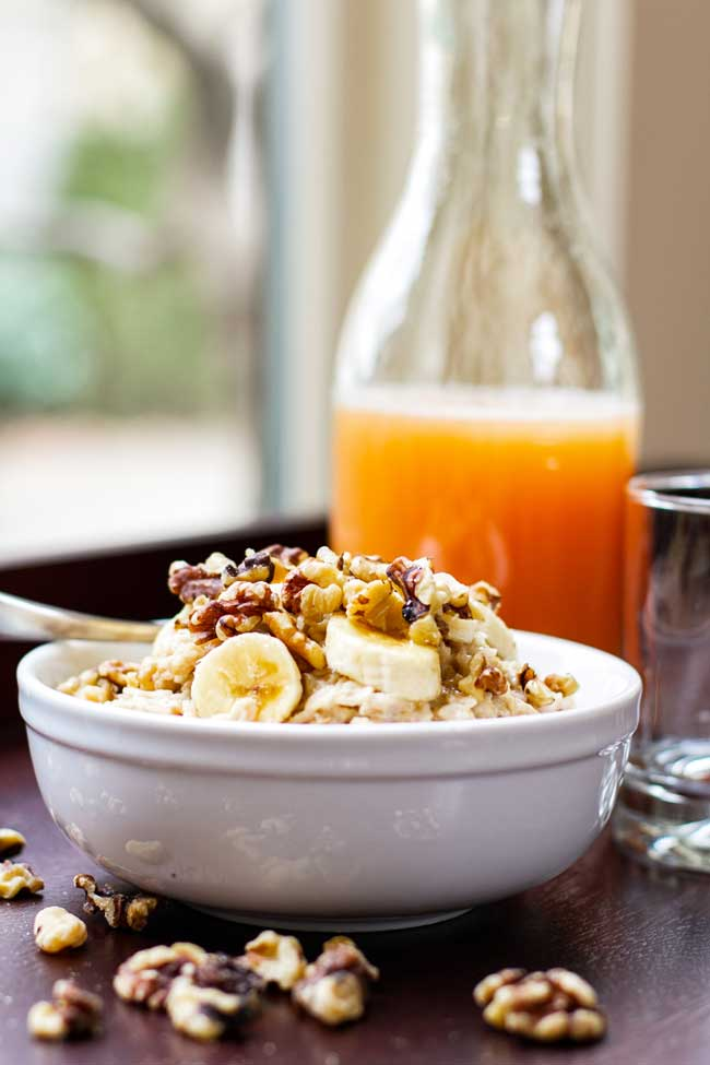 banana nut oatmeal with a jug of grapefruit juice in the background