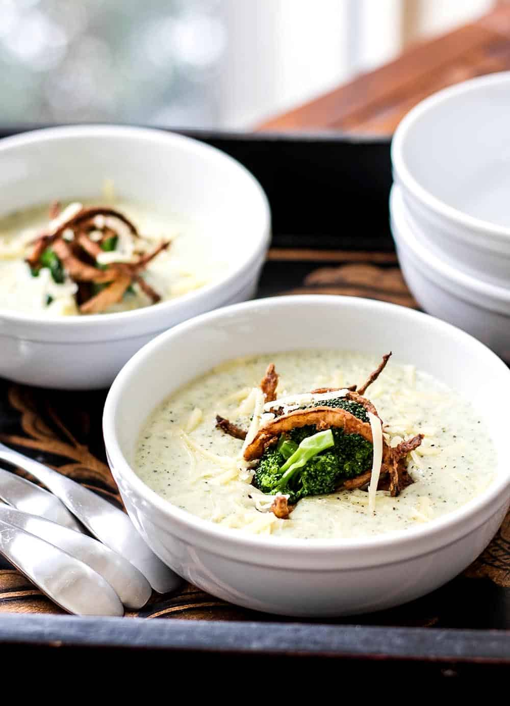 Two bowls of broccoli cheese soup on a tray