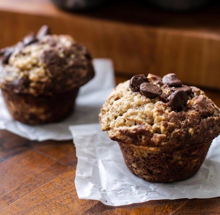 Twp peanut butter and chocolate muffins on parchment paper
