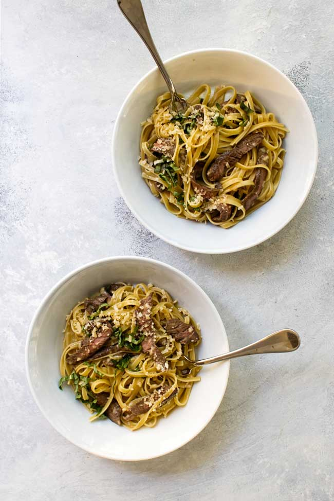 Two bowls of steak carbonara with forks