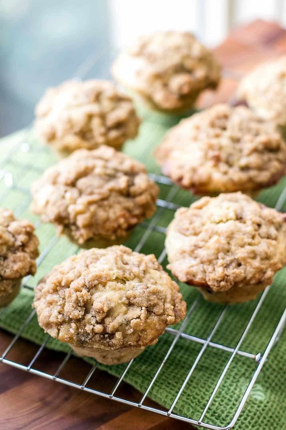 Banana nut muffins lined up on a bakers rack by a window