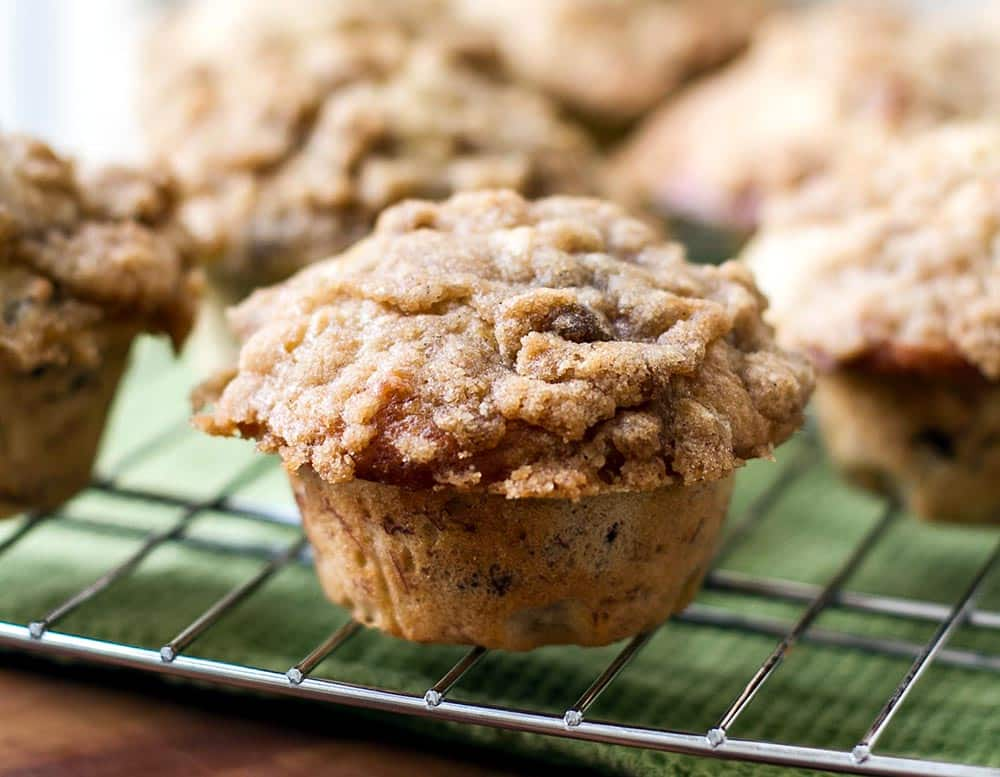 A banana nut muffin on a bakers rack with a green napkin underneath