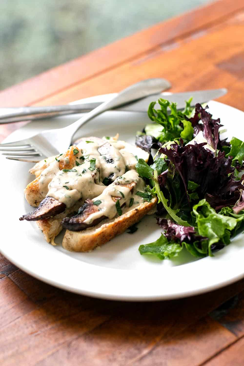 Chicken and Mushroom Supreme on a white plate with salad
