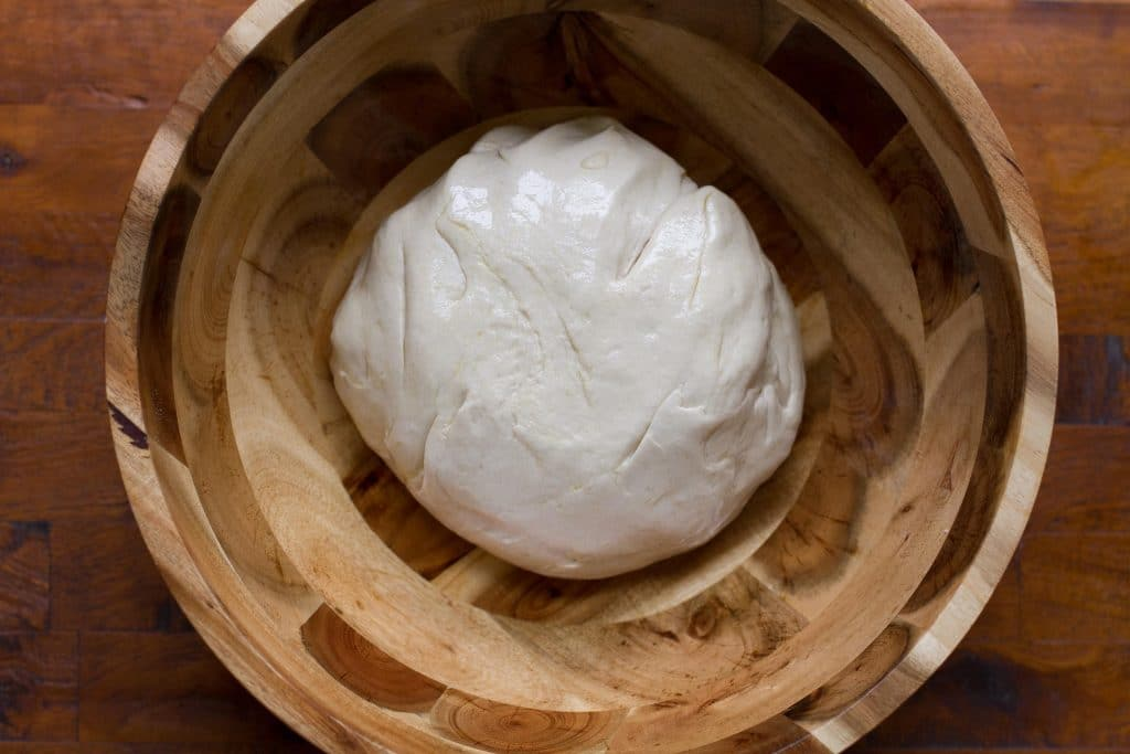 ball of foccacia dough in a wooden bowl