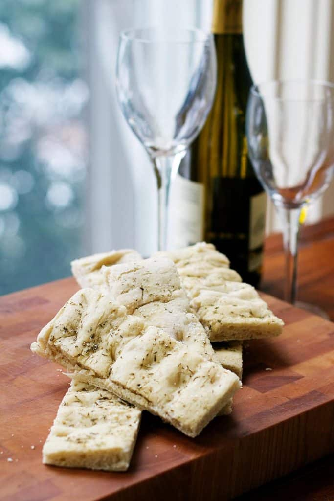 Foccacia on a cutting board with a wine bottle and glasses
