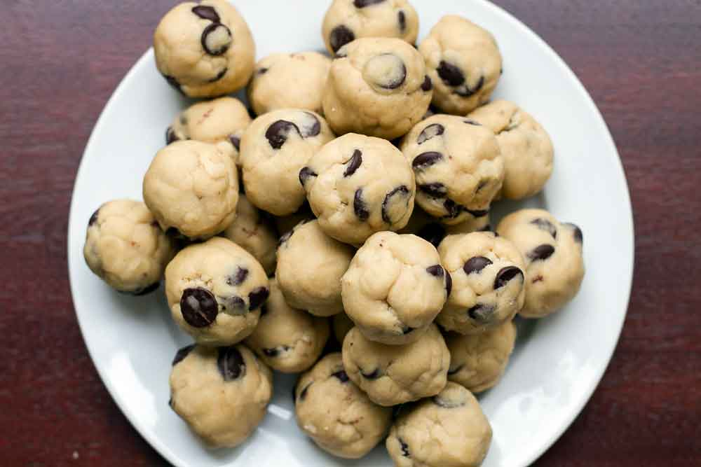 Chocolate chip cookie dough balls on a white plate